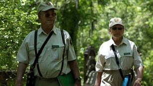 A pair of park rangers walking towards the camera