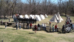 Visitors watching a living history program at a reconstructed Union camp.