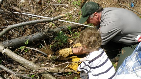 Natural Resource manager and child examine stream