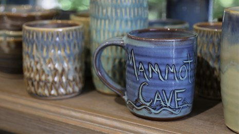 Handcrafted, clay mugs sit on a retail store shelf, ready for sale.