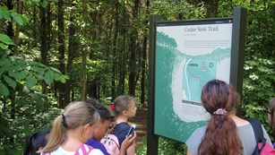Group of hikers reads a trail information board near the Cedar Sink trailhead.
