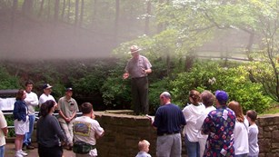 Fog descends as a park ranger addresses a group above the large Historic Entrance  of Mammoth Cave.