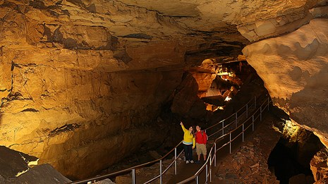 Two park visitors waling along a trail in the cave
