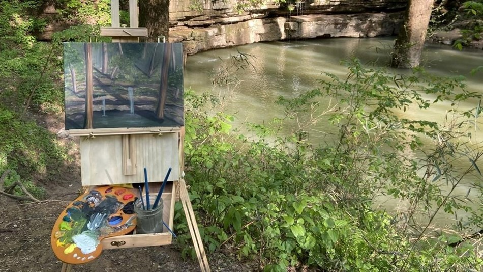 A art easel with a paining and paint set sitting on it. The easel is in front of a natural spring.