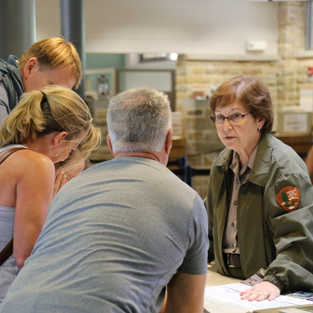 Inside the Mammoth Cave Visitor Center, a ranger answers visitors' questions at the info desk.