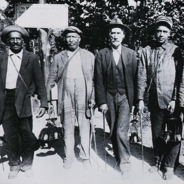 Black and white photo of five men standing for the camera.