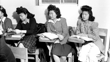 Black and white photo of three young women working at desks at Manzanar