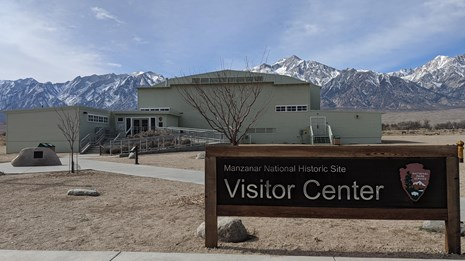 Foreground Visitor Center sign, background faded green auditorium in front of snow capped mountains