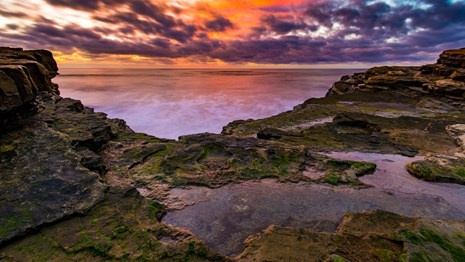 Colorful sunset reflected in the ocean and tidepools at Cabrillo National Monument