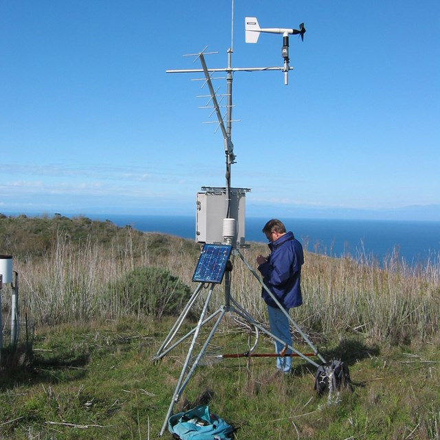 Person standing alongside a weather station atop a hill overlooking the ocean in Channel Islands NP