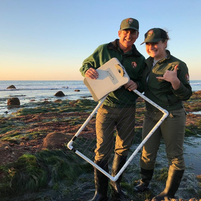 Staff at pose for a photo while collecting rocky intertidal data around sunset at Cabrillo NM