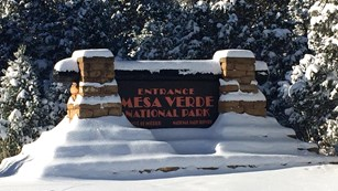 View snow covered park entrance sign.