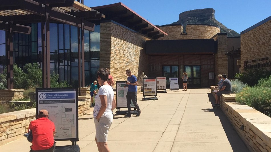 People study signs along a walkway in front of a large stone visitor center building