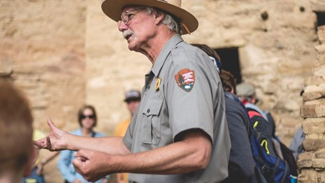 A ranger with white hair and mustache gestures with hands while visitors gather around listening