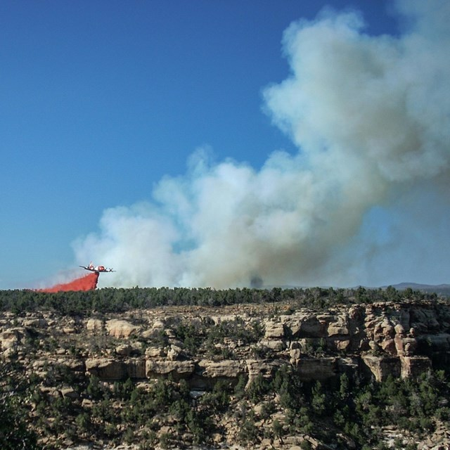 Plane dropping red fire retardant on wildfire