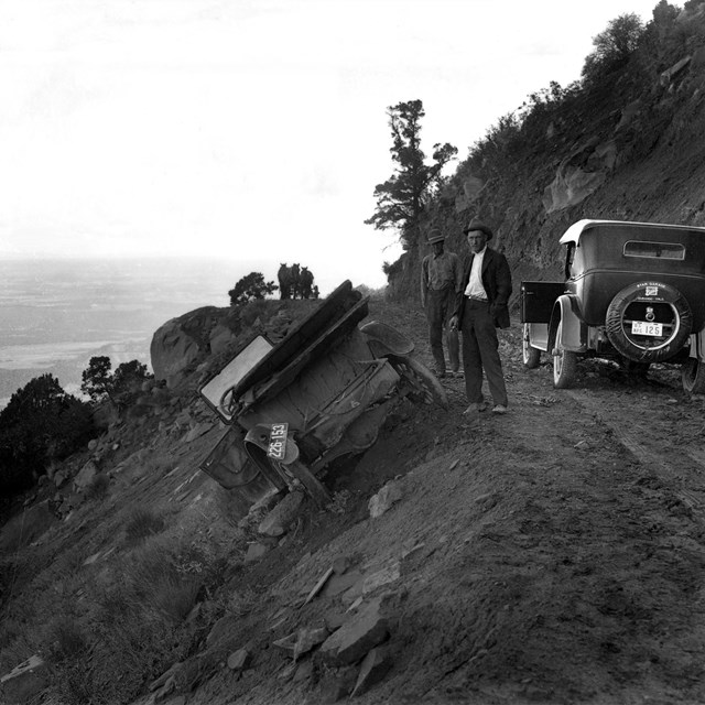Two early vehicles on a dirt road that traverses a steep hillside. One is has gone off the road.