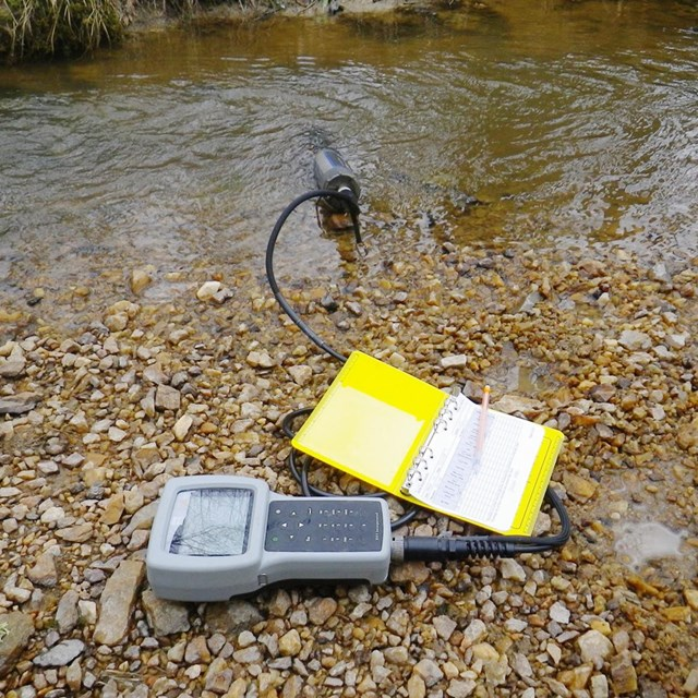Device recording water chemistry at the edge of a stream beside a data sheet and pencil