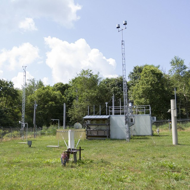 Climate monitoring station in a grassy clearing, with many scientific instruments scattered about.