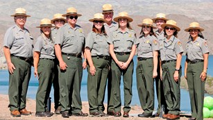 Eleven people wear an National Park Service Uniform standing in front of a lake.