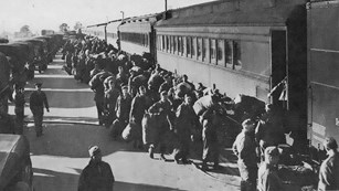 Hundreds of soldiers on platform boarding trains.