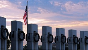 Pillars of white granite with brass wreaths are silohouetted against a pink sky.