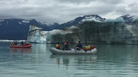 A raft full of people in Alsek Lake with Glaciers in the background.