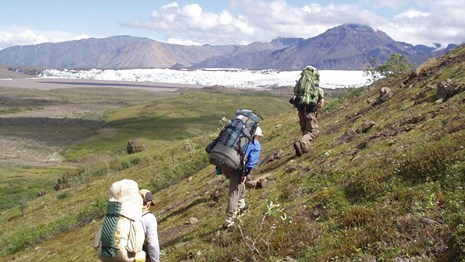 Three backpackers spaced out on the trail with mountains in the background.