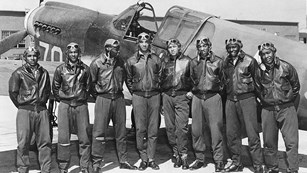 World War II Tuskegee Airmen standing in front of plane.