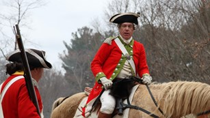 A British officer on horseback converses with an officer on foot