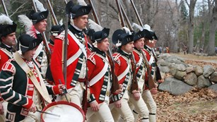 A group of 8 men dressed as Revolutionary War British soldiers with red coats, muskets and one drum.