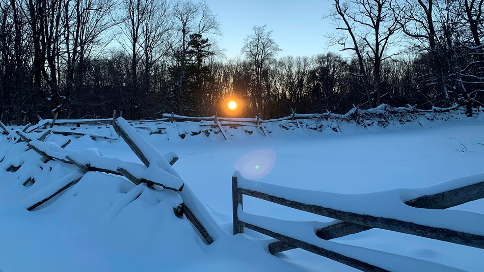 Sun setting behind bare trees in a snow-covered landscape with stone walls, wooden fences and field