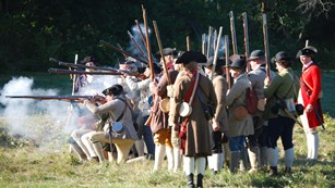 Group of 40 men dressed as Revolutionary War militia soldiers firing their muskets, white smoke.