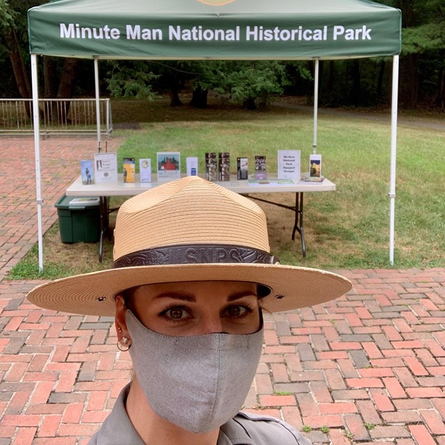 Female ranger wearing a mask that covers her nose and mouth stands in front of an outdoor info table