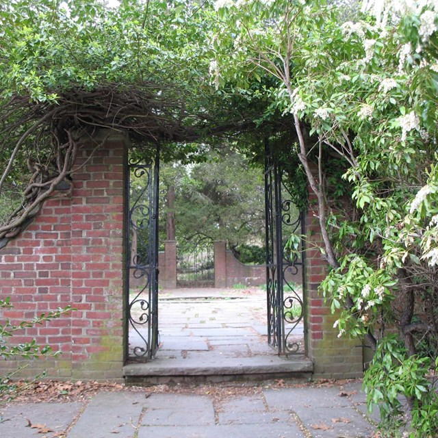 Gateway of red brick and iron stands open and surrounded by bushes