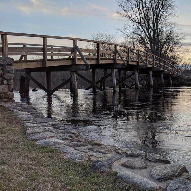 A wooden bridge spans a small river at sunset