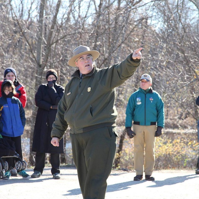 A National Park Ranger surrounded by visitors points off camera while speaking