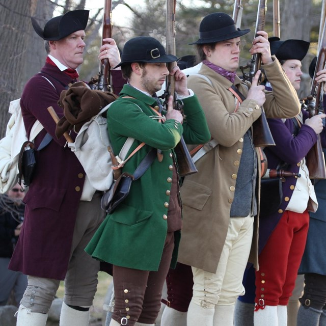 colonial reenactors, dressed in non-uniform clothing, perform drill with their muskets