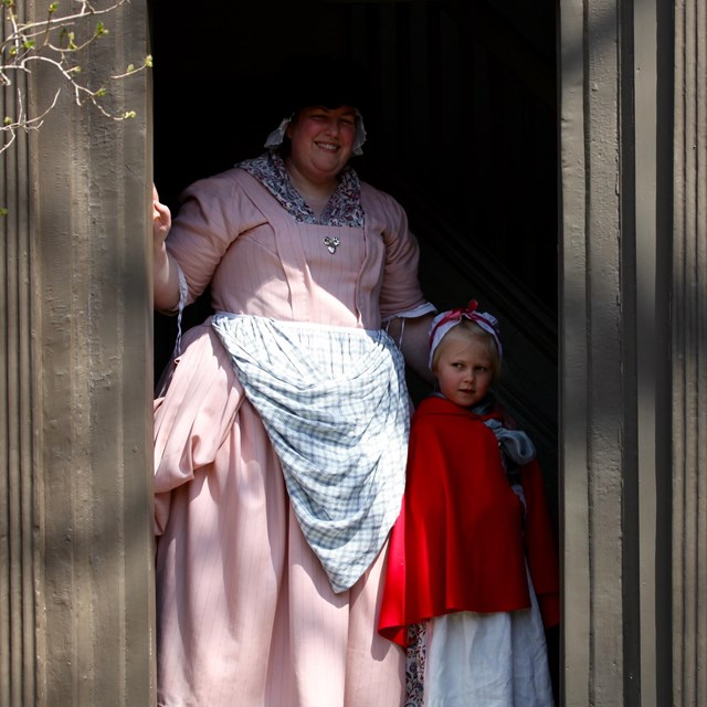 woman and young girl dressed in colonial clothing stand in the doorway of a brown colonial house