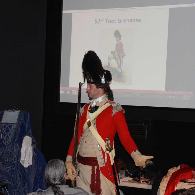 Park volunteer dressed in British Army uniform gives a presentation of his research
