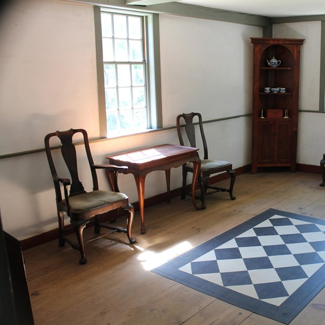 A room in a historic house with a wooden floor, checkerboard floor cloth, side chairs and a table