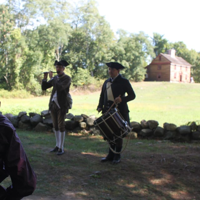 A colonial fifer and drummer stand in front of a stone wall. A colonial house is in the background.