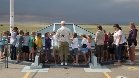 Students and a volunteer stand at the Delta-09 missile silo
