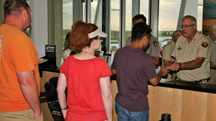 Visitors wait to be served by a park volunteer at an informaiton desk