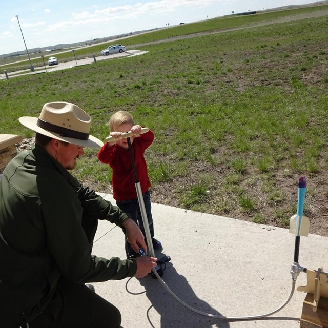 A park ranger assists a young boy with launching a paper rocket