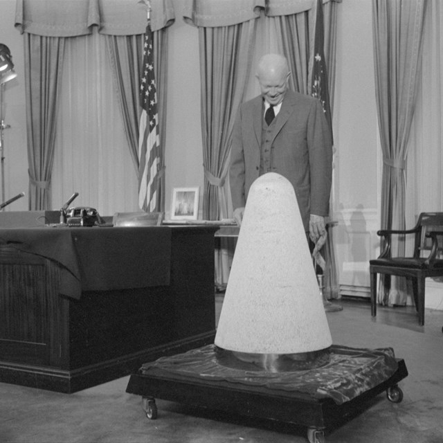 President Eisenhower looks at a missile nosecone in the Oval Office