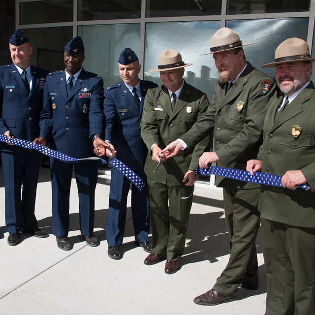 Air Force officers and park rangers cut a ribbon in front of the visitor center