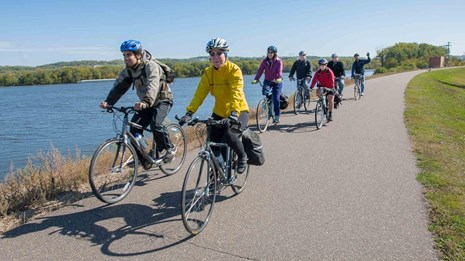 Bicyclists ride a trail beside a river.