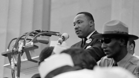 Black and white photo of Dr. Martin Luther King Jr. at a podium and park ranger in the foreground