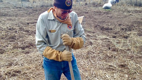 Volunteer digging in the dirt with a shovel