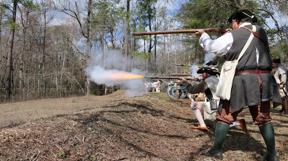 Patriot Militia fire their muskets from behind earthworks